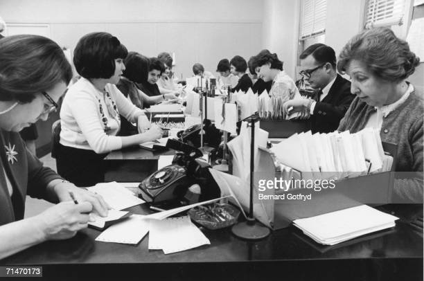 Male and female employees do paperwork at small cluttered desks at the brokerage house of Merrill Lynch Fenner Smith New York 1965
