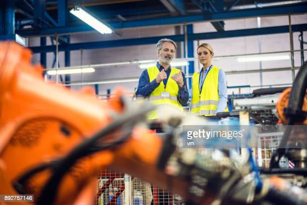 Male and female engineer looking at robotic arms