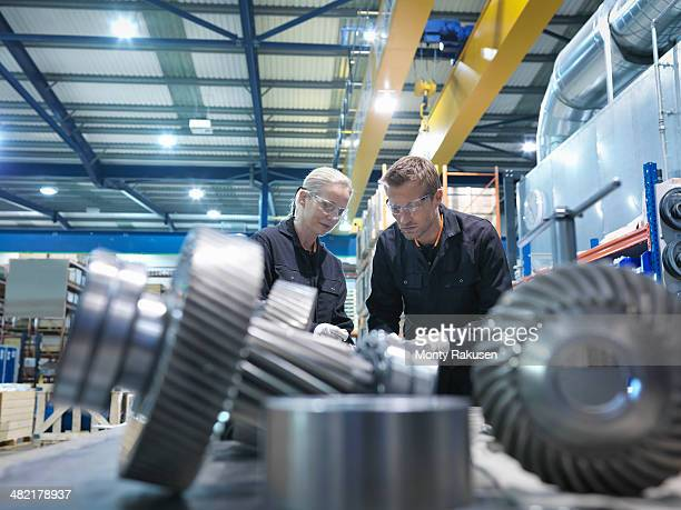 Male and female engineers assembling industrial gearbox in engineering factory