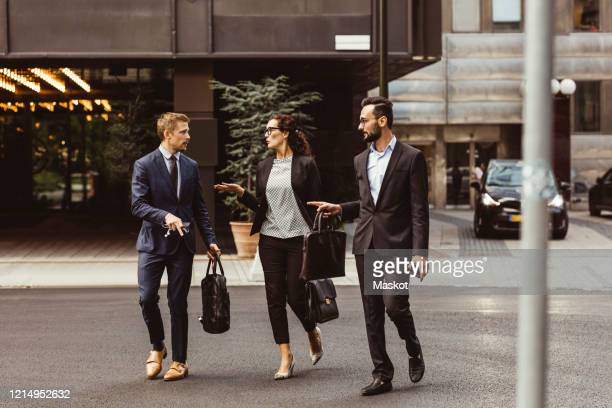 male and female entrepreneurs discussing business strategy while walking outdoors - nur erwachsene stock-fotos und bilder