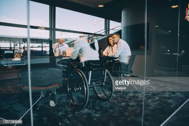 male and female entrepreneurs planning strategy during meeting in board room at creative office - disability stock pictures, royalty-free photos & images
