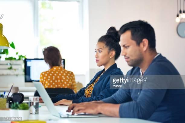 mannelijke en vrouwelijke ondernemers die in bureau zitten - izusek stockfoto's en -beelden