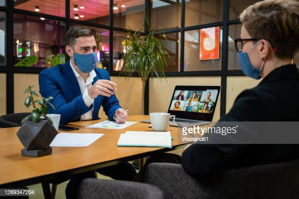 male and female entrepreneurs wearing masks while planning strategy in board room during pandemic - interview stock pictures, royalty-free photos & images