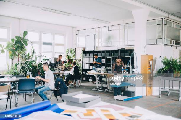 male and female entrepreneurs working in creative office - design studio stock pictures, royalty-free photos & images