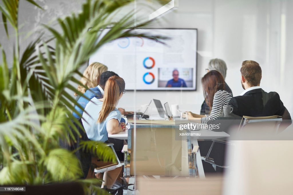 Male and Female Executive Team Video Conferencing with CEO : Stock Photo