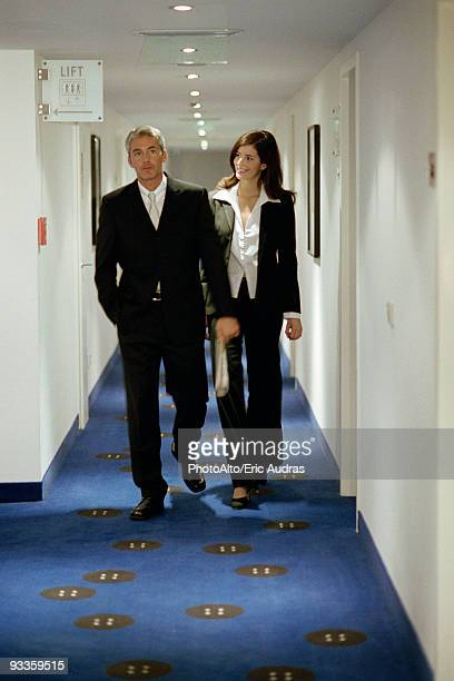 Male and female executives walking in hotel corridor