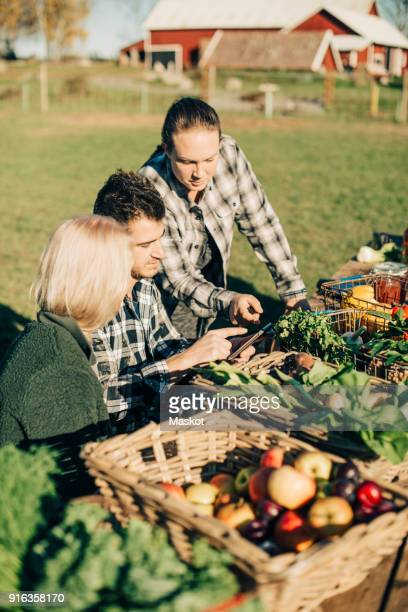 Male and female farmers using digital tablet with organic vegetables on table