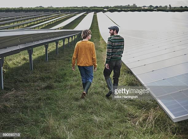 Male and female farmers walking through solar farm