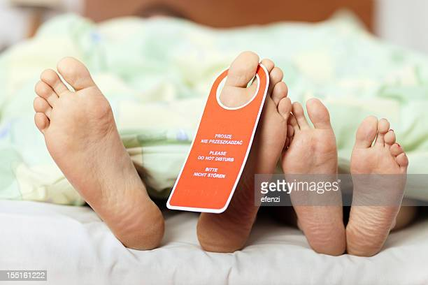 Male and female feet in bed with aDo Not Disturb sign on toe