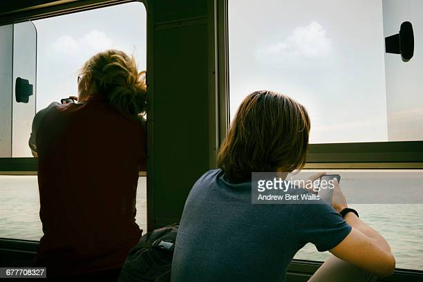 Male and female ferry travellers mobile texting