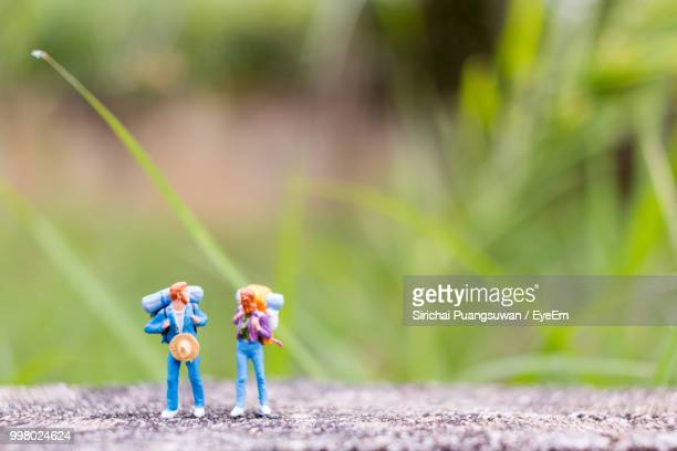 male and female figurines on footpath - small stock pictures, royalty-free photos & images
