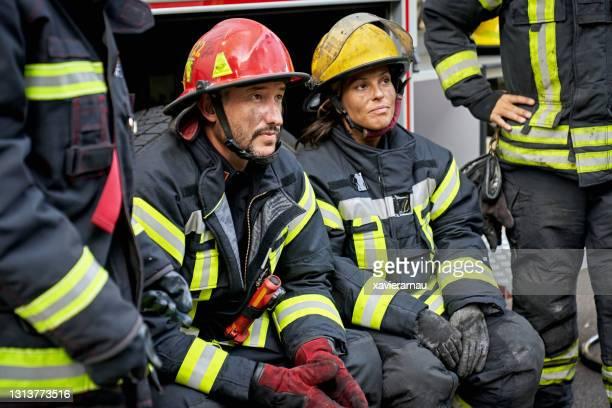 休憩中の男性と女性の消防士 - すす ストックフォトと画像