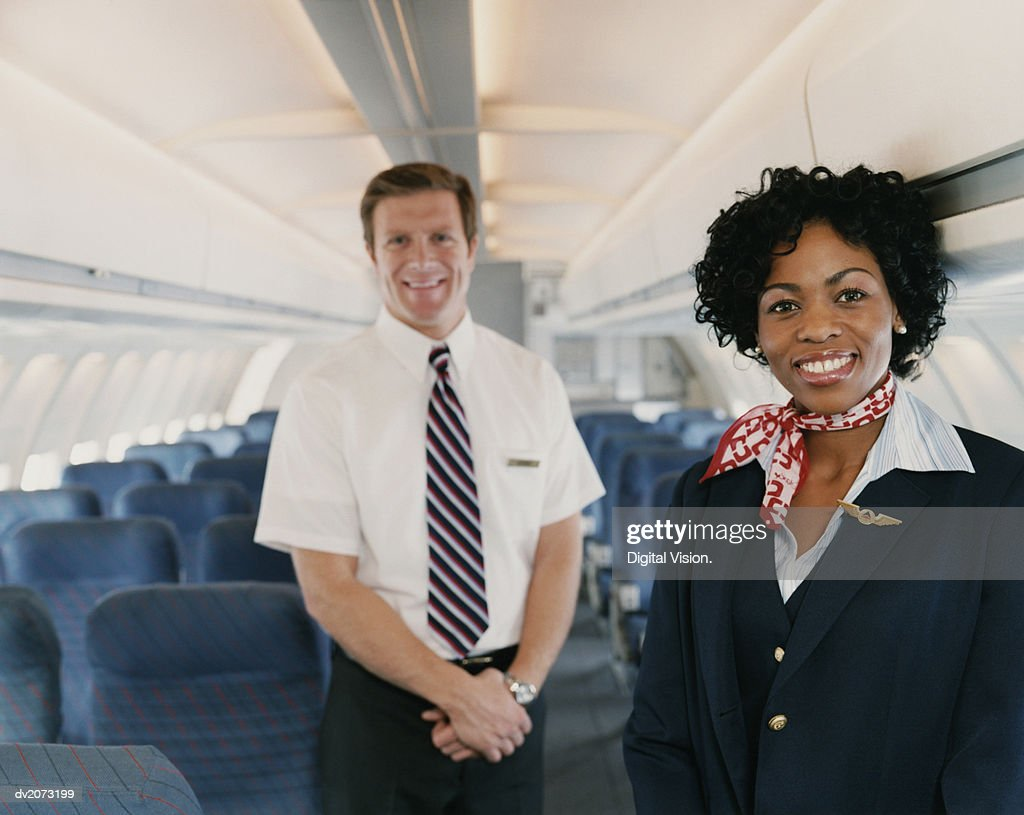 Male and Female Flight Attendants in the Cabin of a Plane : Stock Photo