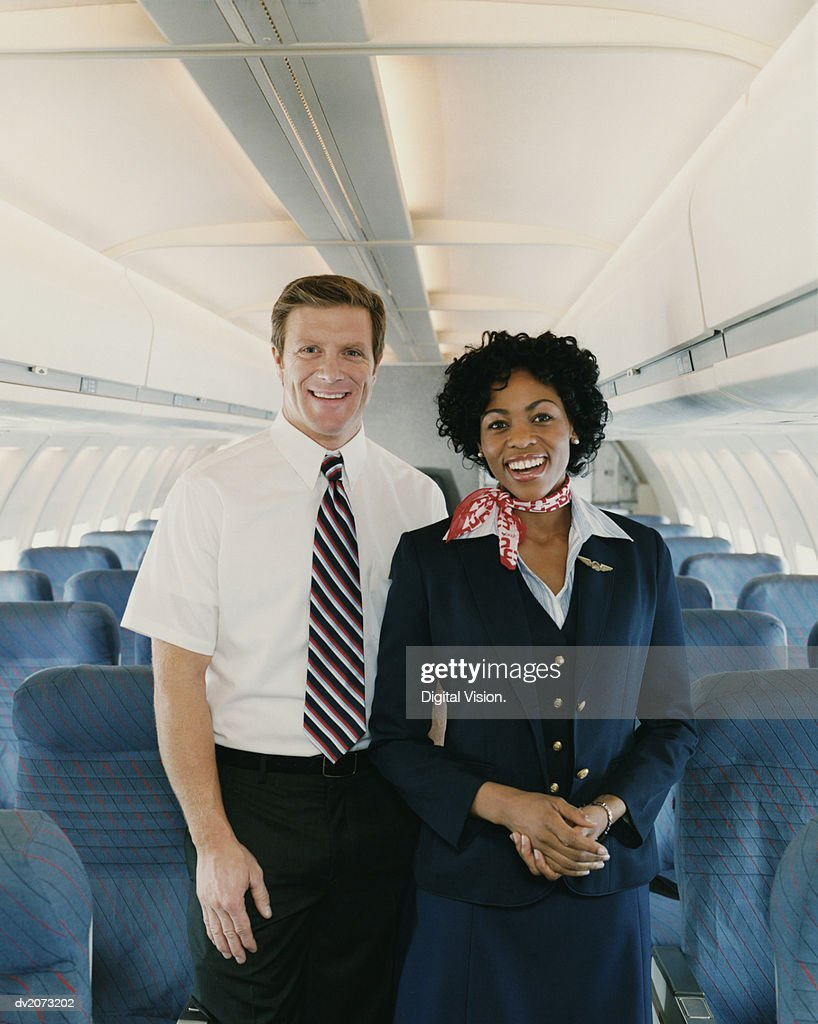 Male and Female Flight Attendants on a Plane : Stock Photo