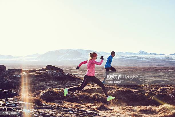 Male and Female free running through mountains