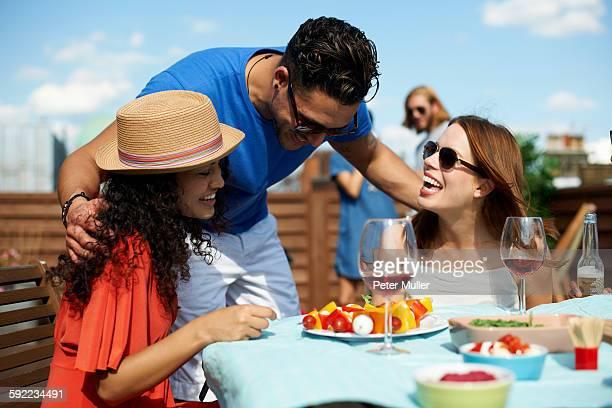 Male and female friends chatting at rooftop barbecue