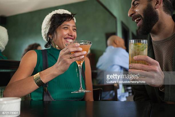 male and female friends drinking cocktails in recreational bar - heshphoto stock pictures, royalty-free photos & images