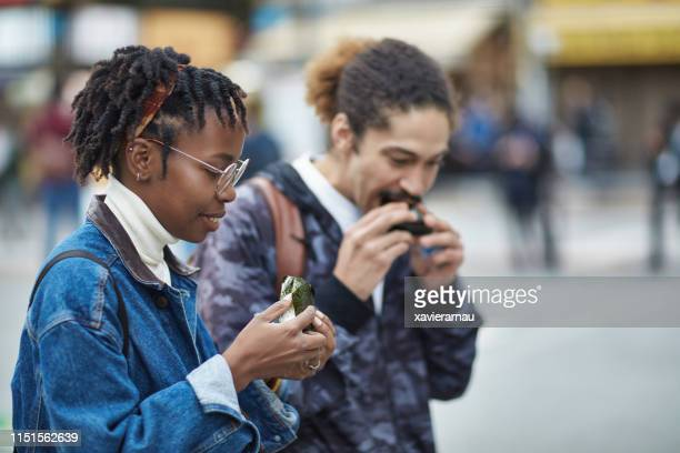 male and female friends eating rice balls in city - rice ball stock pictures, royalty-free photos & images