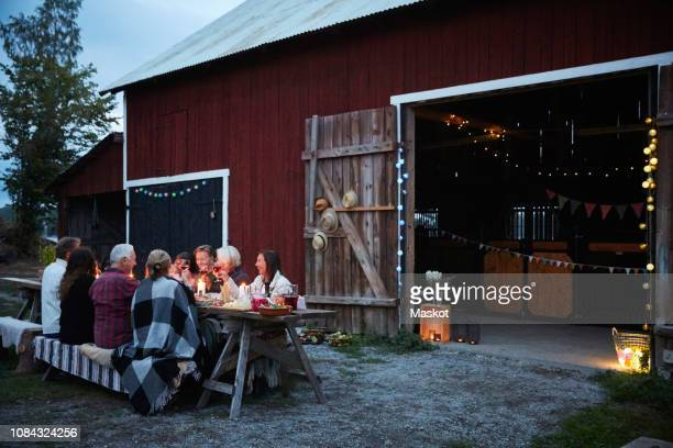 male and female friends enjoying dinner party against barn at farm - ファームハウス ストックフォトと画像