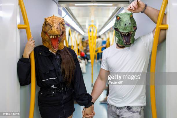 male and female friends holding hands while wearing dinosaur mask in train - mask disguise stock pictures, royalty-free photos & images