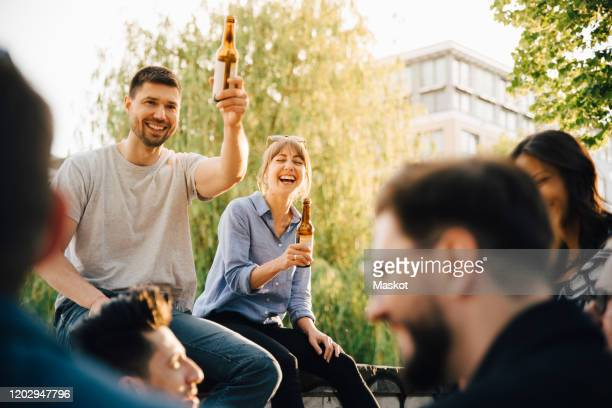 male and female friends laughing while sitting at social gathering - men friends beer outside stock pictures, royalty-free photos & images