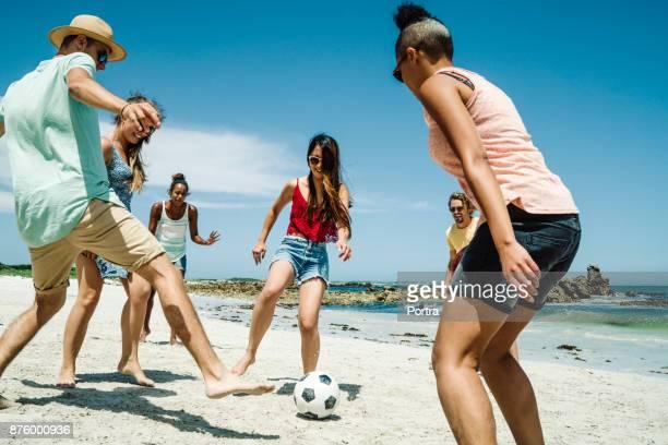 masculinos e femininos amigos jogando futebol na praia - sporting term - fotografias e filmes do acervo