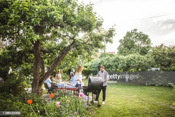 male and female friends preparing food on barbecue while family having fun in backyard - barbecue social gathering stock pictures, royalty-free photos & images