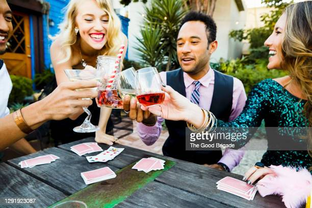male and female friends raising toast while enjoying party at back yard - honour stock pictures, royalty-free photos & images