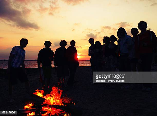 male and female friends standing by bonfire on beach during sunset - bonfire stock photos and pictures