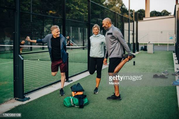 male and female friends stretching by net in sports court - stretching stock pictures, royalty-free photos & images