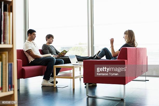 Male and female friends studying in university library