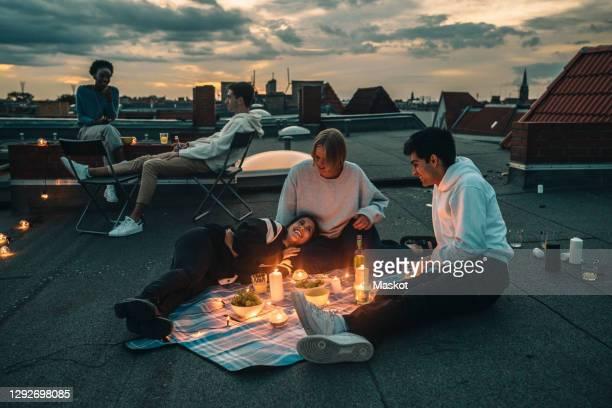 male and female friends talking on building terrace during sunset - abenddämmerung stock-fotos und bilder