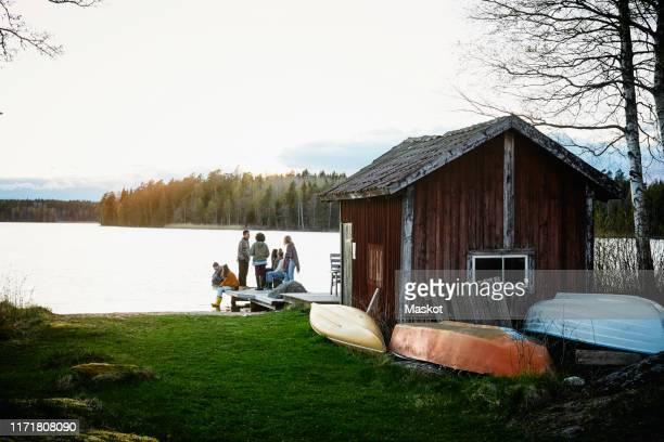 male and female friends talking outside cottage in front of lake during sunset - pier stockfoto's en -beelden