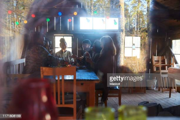 male and female friends talking while enjoying at table in cottage seen through window - photographed through window stock pictures, royalty-free photos & images
