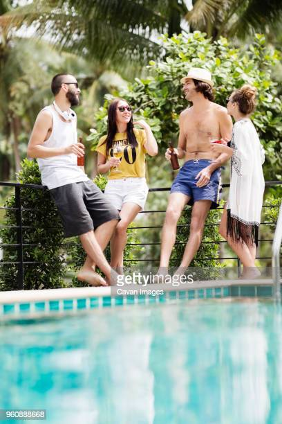 Male and female friends talking while having drinks at poolside