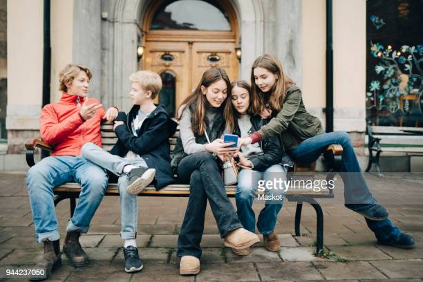male and female friends talking while sitting on bench in city - 12 13 anni foto e immagini stock