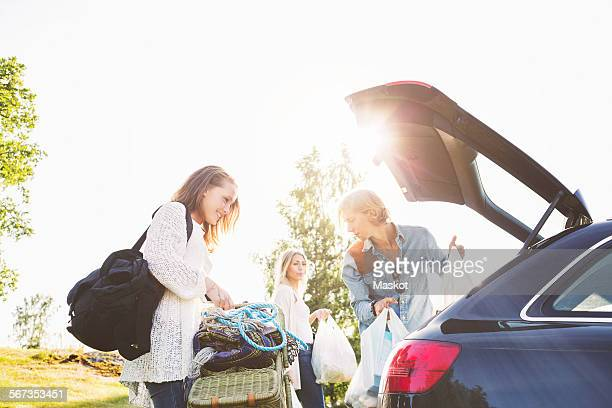 Male and female friends unloading car on field against clear sky