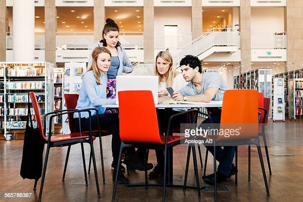 Male and female friends using laptop together at table in library