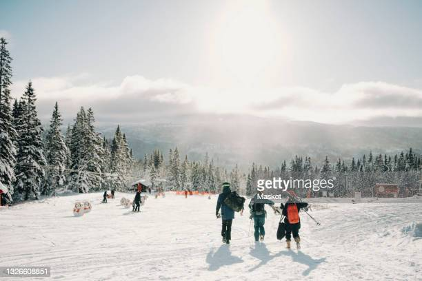 male and female friends walking at tourist resort during winter - sweden stock pictures, royalty-free photos & images