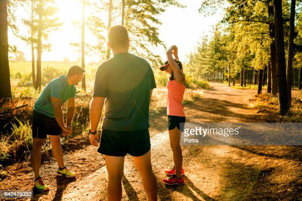Male and female friends warming up before jogging