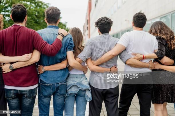 male and female friends with arms around standing on footpath in city - zij aan zij stockfoto's en -beelden
