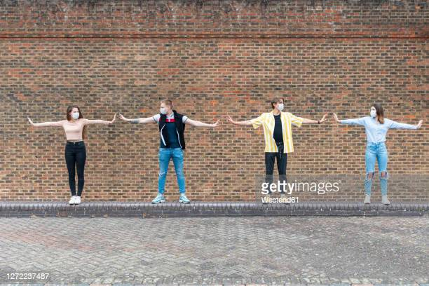 male and female friends with arms outstretched maintaining safe distance while standing against brick wall - protection stock pictures, royalty-free photos & images