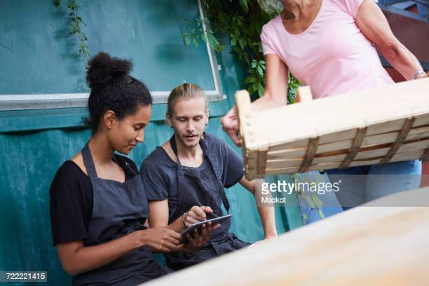 Male and female gardener using tablet computer while senior woman carrying crate in yard