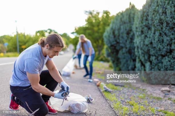 コミュニティサービスストリートと道端での清掃を行う大学卒業生の男性と女性のグループ - performance group ストックフォトと画像