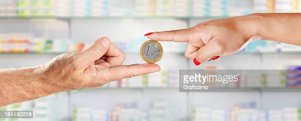 homme et femme mains tenant euro en pharmacie - 1 euro photos et images de collection