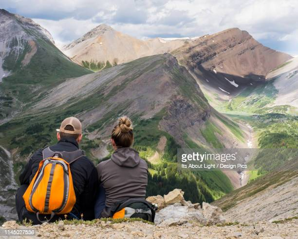 male and female hiker sitting on a rock ridge overlooking a valley and mountain range in kananaskis country - kananaskis country stock pictures, royalty-free photos & images