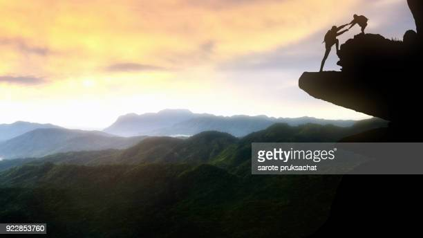 male and female hikers climbing up silhouette mountain cliff and one of them giving helping hand. people helping and, team work concept. - fiducia foto e immagini stock
