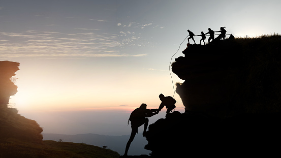 Male and female hikers climbing up silhouette mountain cliff . - gettyimageskorea