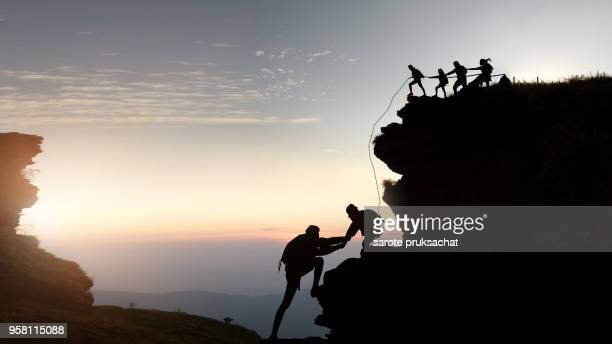 male and female hikers climbing up silhouette mountain cliff . - sportkleding stock pictures, royalty-free photos & images