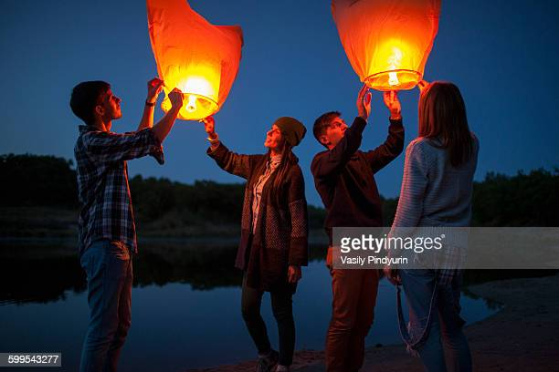 Male and female hikers releasing paper lanterns at lakeshore